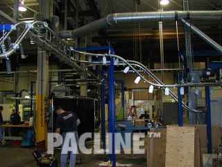 Enclosed track overhead conveyor designed to transfer machined auto parts through wash system.