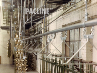 Overhead conveyor carries large racks of metal items through the electroplating process.