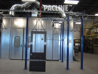Compact overhead conveyor moves Masonite doors through wet spray paint booth and drying ovens.
