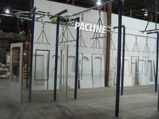 Single line overhead conveyor transfers wooden doors and windows through various stages of paint finishing.