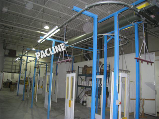 Automated spray paint line uses overhead conveyor to handle tall wooden doors.