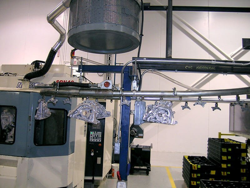 Compact overhead conveyor system to carry metal parts through a chemical wash.