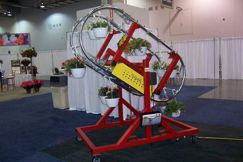 Enclosed track conveyor system for handling hanging plants in greenhouses and growing operations.