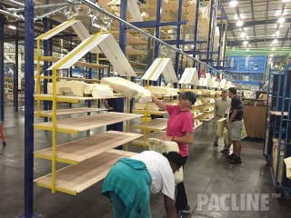 Automotive seat pads are loaded by the operators, onto the overhead conveyor system.