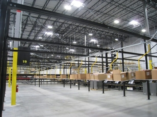 Overhead monorail conveyor for delivery and removal of corrugated cartons in distribution center.