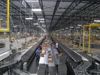 Pacline overhead conveyors deliver empty carton andempty totes in large distribution center.