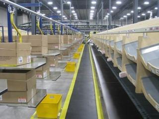 Carton conveyor delivery to sortation chutes in distribution center.