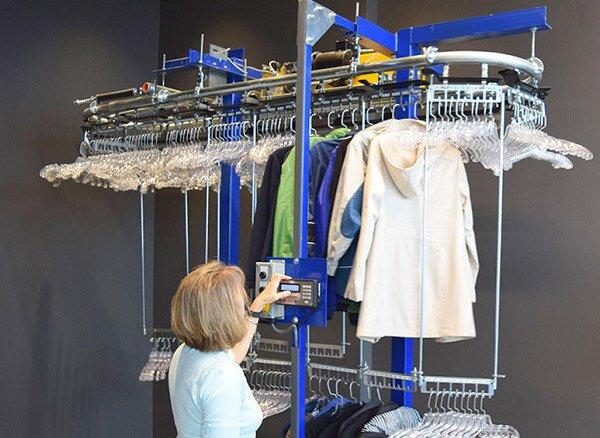 Operator loading garments onto coat check conveyor