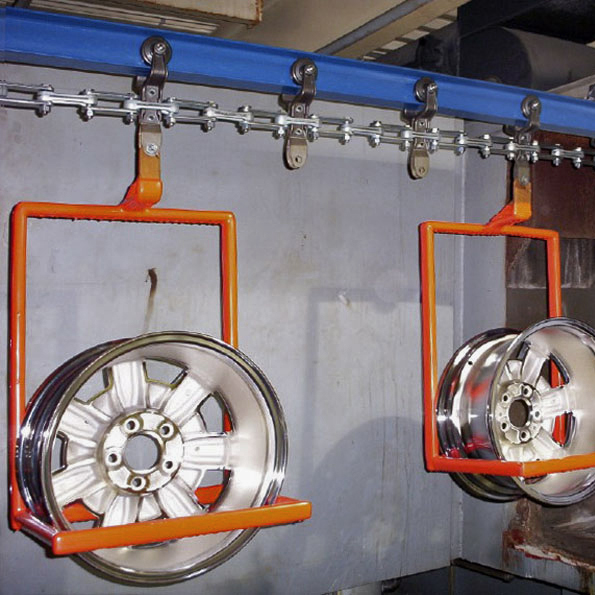 auto rims on conveyor before electroplating